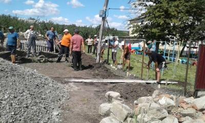 Жителі двох сіл на Буковині спільно робили паркан біля навчальних закладів