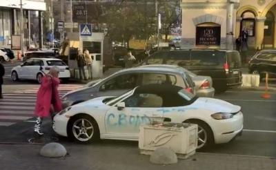 У Києві дівчина розмалювала та порубала сокирою білий кабріолет Porsche (відео)