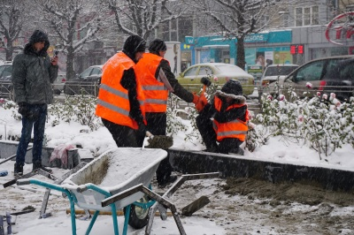 У Чернівцях робітники у снігопад встановлюють бордюри на проспекті - фото