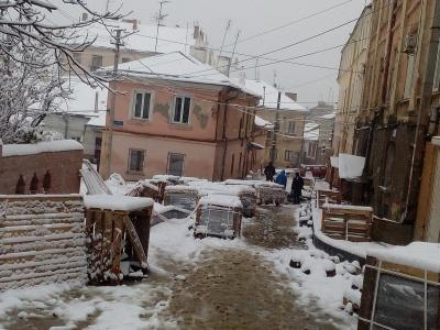 Сніг роботі не завада: робітники продовжують ремонт вулиць в центрі Чернівців