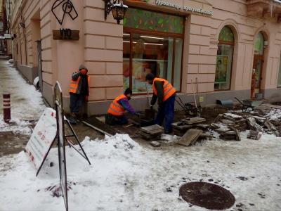 Сніг роботі не завада: на вулиці Кобилянської робітники встановлюють плитку