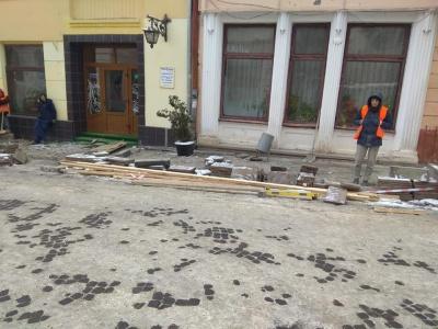 В центре Черновцов рабочие снимают плитку, которую клали в снегопад - фото