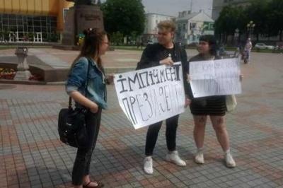 Суд визнав винною в адмінпорушенні дівчину, яка стояла з плакатом за імпічмент Зеленського