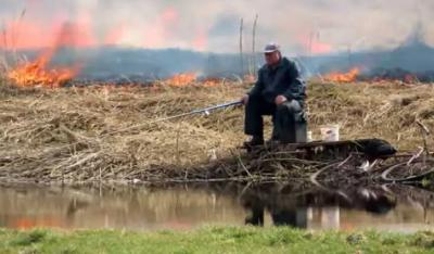 У Білорусі чоловік спокійнесенько рибалив на тлі бурхливої пожежі